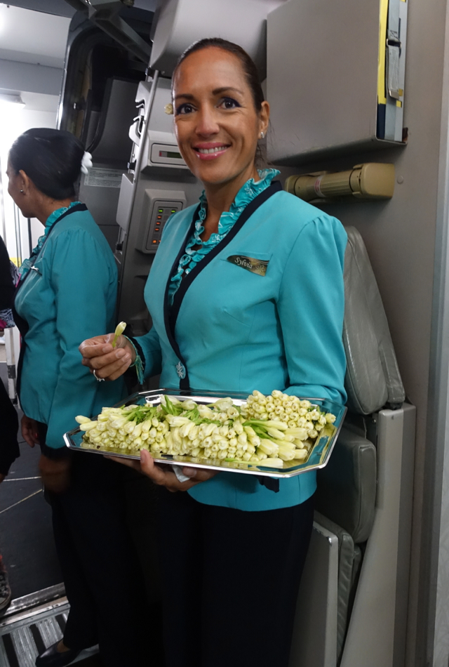 Air Tahiti Nui Flight Attendant Welcoming Passengers with Tiare Flowers
